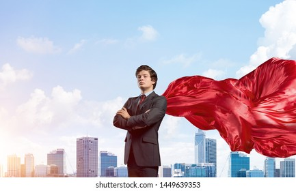 Young confident businessman wearing red cape against modern city background