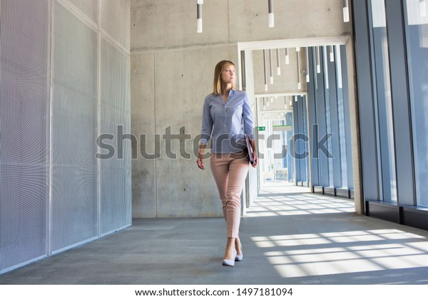 Young confident businesswoman walking while holding document in office