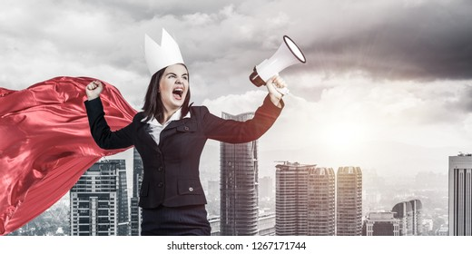 Young confident businesswoman wearing red cape against modern city background screaming in megaphone