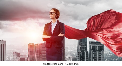Young confident businesswoman wearing red cape against modern city background