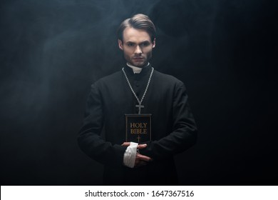young confident catholic priest looking at camera while holding holy bible on black background with smoke - Shutterstock ID 1647367516