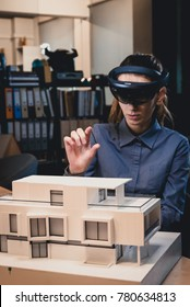 Young confident Caucasian female architect working on a private house project in the office using augmented reality glasses