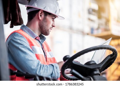 Young confident Caucasian man engineer driving Forklift and wearing white safety helmet and check for control loading containers box from Cargo freight ship for import and export, transport