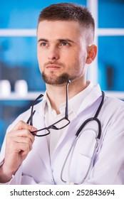 Young confident doctor with glasses is looking away.