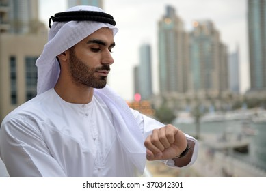 Young confident Emirati man checking time in his wrist watch