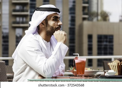 Young confident Emirati man sitting and drinking juice by the canal in Dubai Marina.