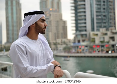 Young confident Emirati man standing by the canal in Dubai Marina