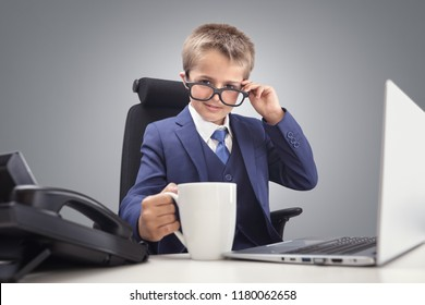 Young confident executive businessman boss boy in office smiling at desk