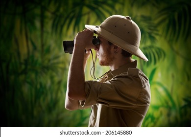Young confident explorer in the rainforest jungle looking through binoculars.