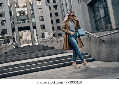 Young and confident. Full length of attractive young woman drinking coffee while walking outdoors