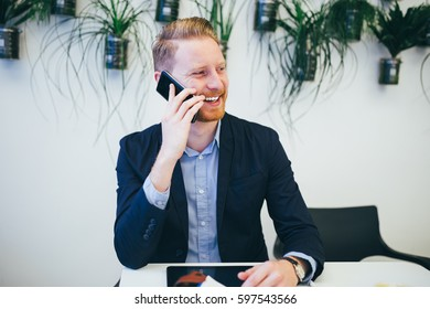 Young confident and happy redhead business man talking on his cell phone and smiling.
