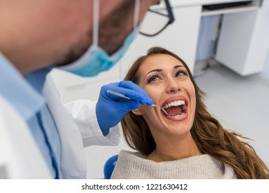 Young confident male dentist Medical treatment to a female patient at the clinic. Dental clinic concept