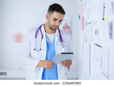 Young and confident male doctor portrait standing in medical off