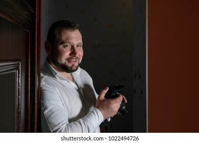 young confident male photographer in a white shirt is holding a camera and watching