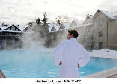 Young confident man in the bathrobe standing near the winter outside spa swimming pool looking away. back view.