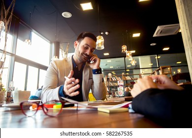 Young confident man in full suit makes work phonecalls working on new project at office