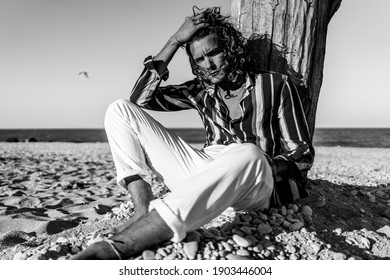 Young confident man portrait at the beach. Black and white image.