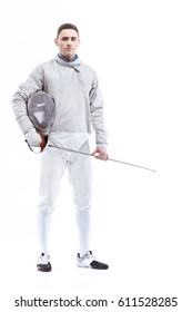 Young confident man professional fencer standing with helmet and rapier   isolated on white