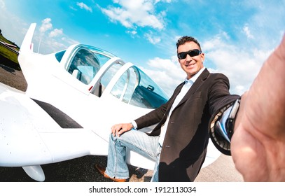 Young confident man taking selfie with mobile smart phone at private airplane - Modern business concept with rich guy ready for luxury excursion