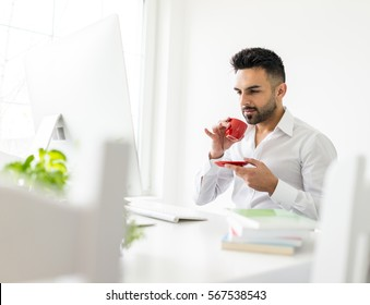 Young confident man working in modern office full of light