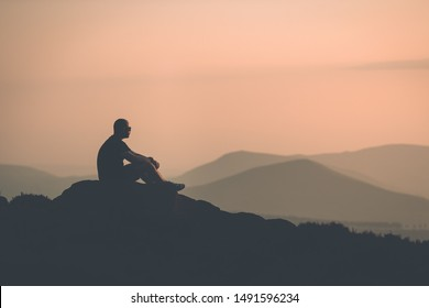 Young confident muscular male sat with a silhouette of mountains in the distance