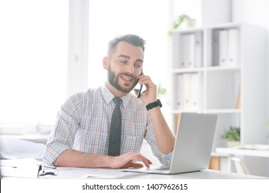Young confident office worker or engineer in shirt and tie consulting someone by phone while looking at latop display by desk