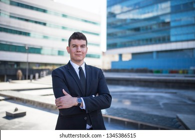 Young and confident politician standing in front of a building