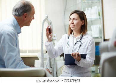 Young confident practitioner with pill-bottle recommending retired man new effective medicine during appointment