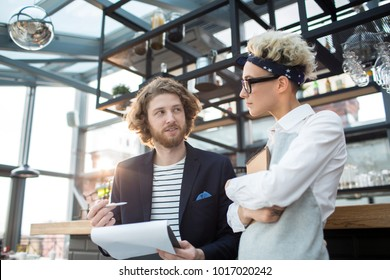 Young confident revision manager or owner of cafe having talk to new waitress at the beginning of her first working day