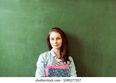 Young confident smiling female high school student standing in front of chalkboard in classroom, holding textbooks, looking at camera. Waist up portrait.