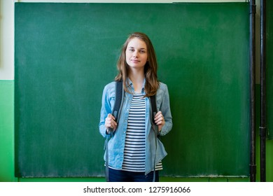 Young confident smiling female high school student standing in front of chalkboard in classroom, wearing backpack, looking at camera. Waist up portrait.