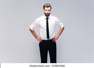 Young and confident. Studio shot of handsome young man in shirt and tie holding hands on hip and looking at camera