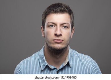 Young confident successful male ceo in blue shirt looking at camera over gray background