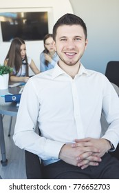 a young confident successful man, an office worker, in a white shirt smiles, in the background two girls work