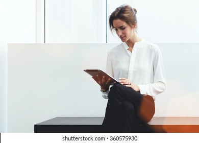 Young confident woman entrepreneur chatting on digital tablet with client while sitting on bench in office interior, intelligent female lawyer in formal wear reading electronic book during work break