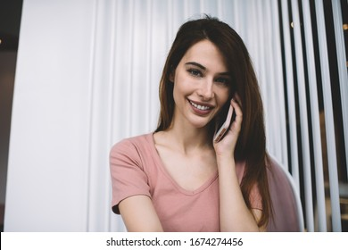 Young confident woman with long dark hair in casual pink T-shirt having phone conversation on smartphone while sitting in cafe looking at camera