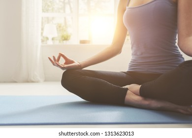 Young confident woman practicing mindfulness meditation at home, she is sitting with crossed legs on a mat