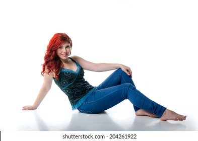 Young confident woman sitting barefoot on the floor, isolated on white background