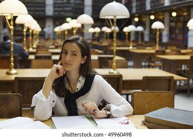 Young confident woman sitting at desk in old university library with books and note pad.