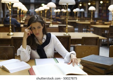 Young confident woman sitting at desk in old university library with books and note pad contemplating.