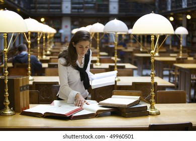 Young confident woman standing at desk in old university library studying books.