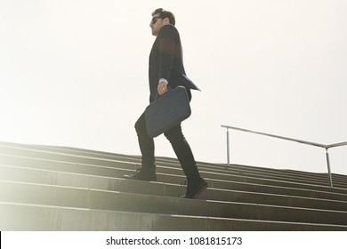 Young confidental businessman wearing suit and running fast upstairs. Horizontal outdoors shot.