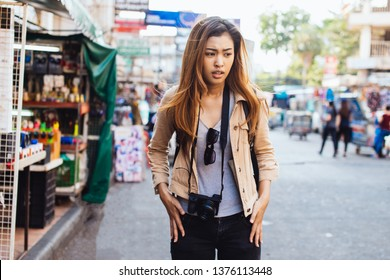 Young confused Asian woman checking pockets of jeans finding loss of stuff while traveling in city