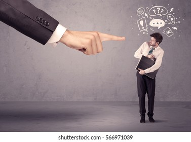 A young confused businessman being fired by large boss hand concept with drawn speech bubbles, exlamation, question marks
