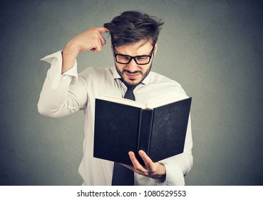 Young confused man scratching head while trying to read smart book misunderstanding content.