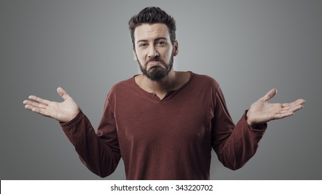 Young confused man shrugging and looking at camera