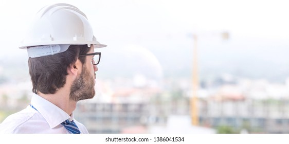 Young construction engineer with helmet is checking the construction of the building. Dressed in white shirt, eyeglasses, blue tie and long beard.