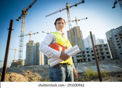 Young construction manager posing on building site at sunny day