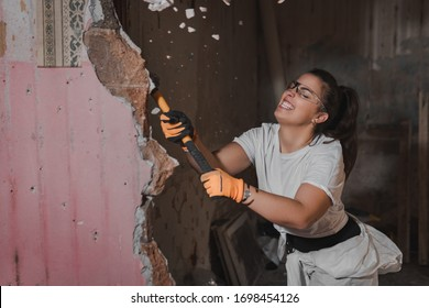 Young construction woman in white working outfit clothes hitting hard and breaking a wall with a large heavy hammer  during manly renovation work