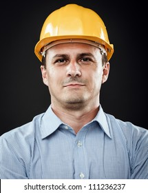Young construction worker in hard hat on gray background